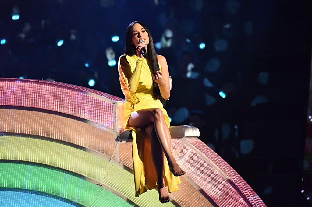 "Hold tight to your umbrella, because Kacey Musgraves's iHeartRadio Music Awards performance is about to blow you away. On Thursday, the singer gave a magical performance of her song ""Rainbow"" alongside Coldplay's Chris Martin. The Grammy winner looked like an actual pot of gold as she sat on top of a neon rainbow while donning a gorgeous yellow dress. Prepare to get lost in her beautiful performance ahead!"