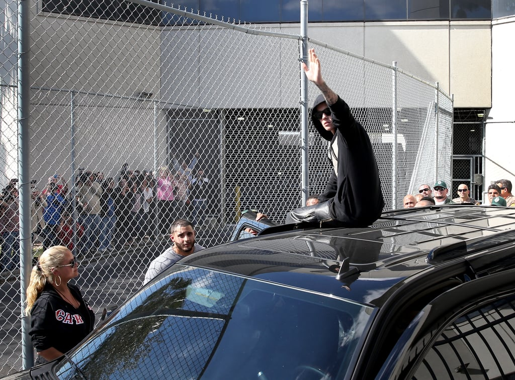 "After being released on a $2,500 bond, Justin Bieber left the Miami-Dade County jail on top of his black SUV while waving to gathered fans. With police officers looking on, Justin hopped onto the roof of the car while wearing the black sweatshirt and leather shorts he was arrested in. Justin was arrested early Thursday morning under suspicion of DUI when he was pulled over for speeding. According to the police report, Justin initially resisted arrest and refused to cooperate with the officer. After giving Justin a field sobriety test, which he failed, the officer placed him under arrest and took him into the station for another sobriety test, which he also failed. A police spokesman said that Bieber also admitted to smoking marijuana and taking ""some prescription medication"" before his arrest. He was charged with a DUI, resisting arrest, and driving with an invalid license.  Source: Getty / Joe Raedle"