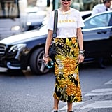 A graphic tee is fun with a printed midi skirt and embellished slides.