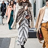 While leaving the Zimmermann show, Olivia snuggled up in a fur jacket that she wore on top of her striped Zimmermann dress.