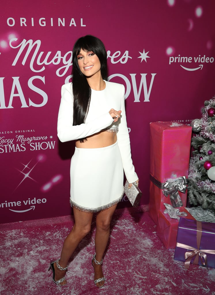 Kacey Musgraves looked like she stomped right out of a Winter wonderland when she arrived at a celebration for her upcoming Amazon Prime Video holiday special. At the New York City screening of The Kacey Musgraves Christmas Show on Nov. 19, the country singer debuted new bangs while wearing an all-white David Koma set with a crystal hem that doesn't not look like tinsel. Kacey completed her look with Eva Fehren rings and earrings, as well as Stella Luna sandal heels. With their metallic material and chain-link ankle strap, the heels are perfect for all those forthcoming holiday parties. Plus, it seems like Santa got the message, because they're currently 30 percent off at Shopbop. Shop Kacey's festive 'fit ahead.      Related:                                                                                                           Yeehaw Queen? Kacey Musgraves Is More Like a Fashion Queen in These Iconic Looks