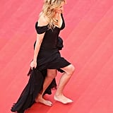 """Julia made a case against the Cannes """"no flats"""" policy by giving up her heels and walking the red carpet barefoot in 2016. Her Giorgio Armani Privé gown was finished with an emerald Chopard necklace."""