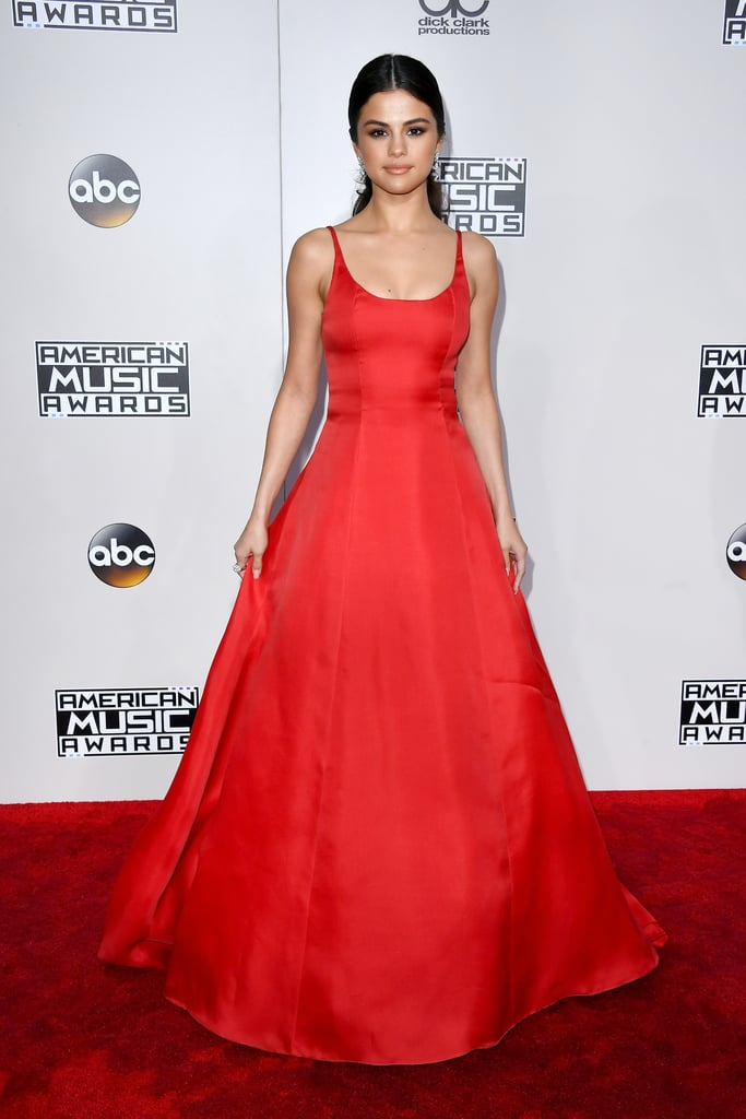 "The rumors were true! Selena Gomez did, indeed, make her first public appearance since taking a break from the limelight to focus on her health at the 2016 American Music Awards on Nov. 20. The ""Kill Em With Kindness"" singer turned heads in a bright red Prada teacup gown fit for a princess — and a rerevival, of course. Selena, who was completely glowing, kept all eyes on the striking number with a sleek, pulled-back low ponytail, diamond drop earrings, and a soft-yet-smoky beauty look, featuring the perfect nude lip. Keep scrolling to see more pictures of Selena on the AMAs red carpet, then admire her enviable 2016 style.      Related:                                                                                                           A Sexy Look Back at All the Looks Selena Gomez Has Ever Worn to the American Music Awards"