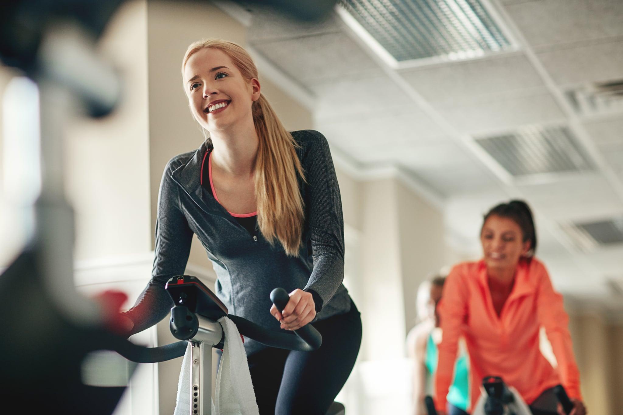Shot of a young woman working out with an exercise bike in a exercising class at the gym