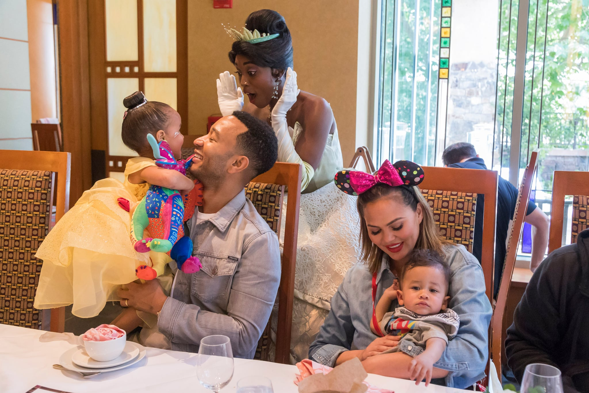 ANAHEIM, CALIFORNIA - APRIL 12: In this handout image, John Legend, Chrissy Teigen, their daughter Luna and son Miles share a moment with Princess Tiana during the Disney Princess Breakfast Adventures at Disney's Grand Californian Hotel on April 12, 2019 in Anaheim, California. (Photo by Joshua Sudock/Disneyland Resort via Getty Images)