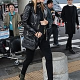 Rosie's airport style stays true to her bohomenian aesthetic. Here, she wore a leather jacket, skinny jeans, and green suede ankle boots. She topped off her ensemble with a black wide-brimmed hat and a fringed scarf by Rockins.