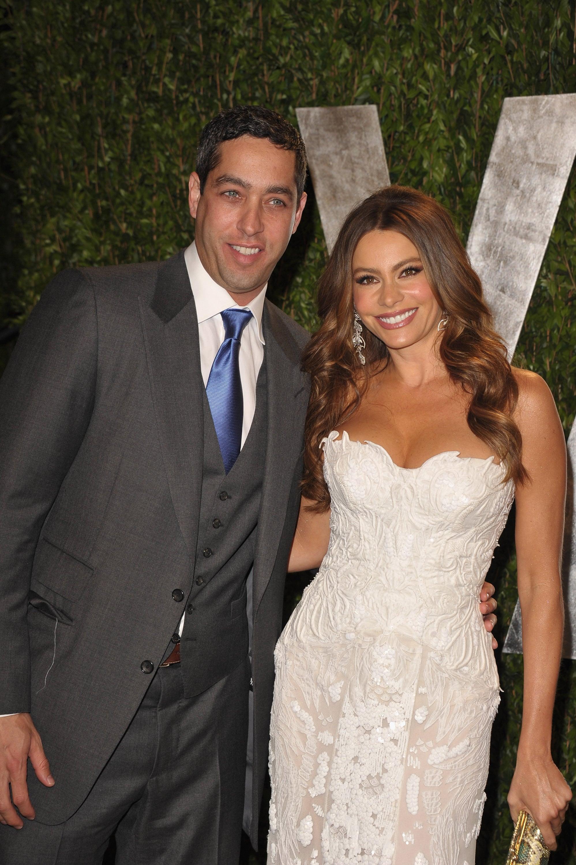 Sofia Vergara in a strapless white lace gown by Roberto Cavalli with boyfriend Nick Loeb.