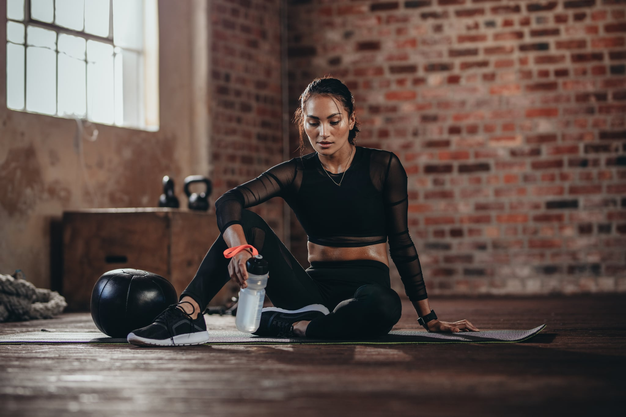 Portrait of a fit young woman taking a break in the gym. Female sitting on fitness mat with a water bottle looking down.
