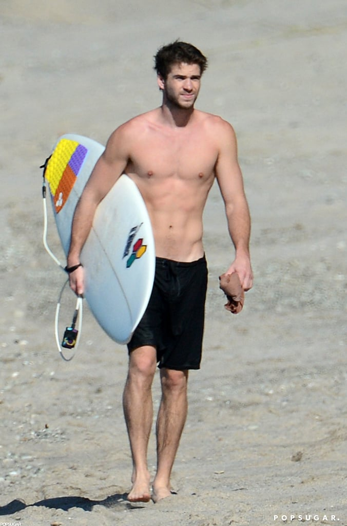 Liam Hemsworth carried his surfboard on the beach.