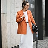 A boldly colored blazer is effortlessly chic for work with a white t-shirt, midi skirt, and pumps.