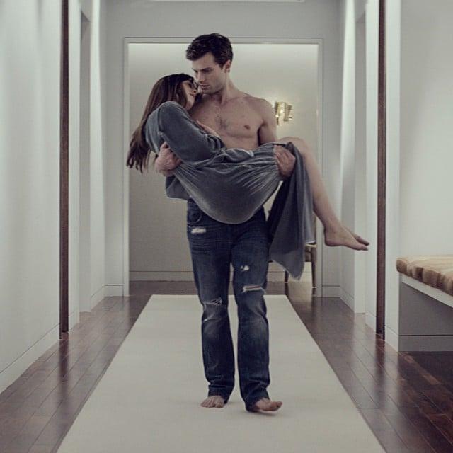 Christian (Jamie Dornan) carries Ana (Dakota Johnson).