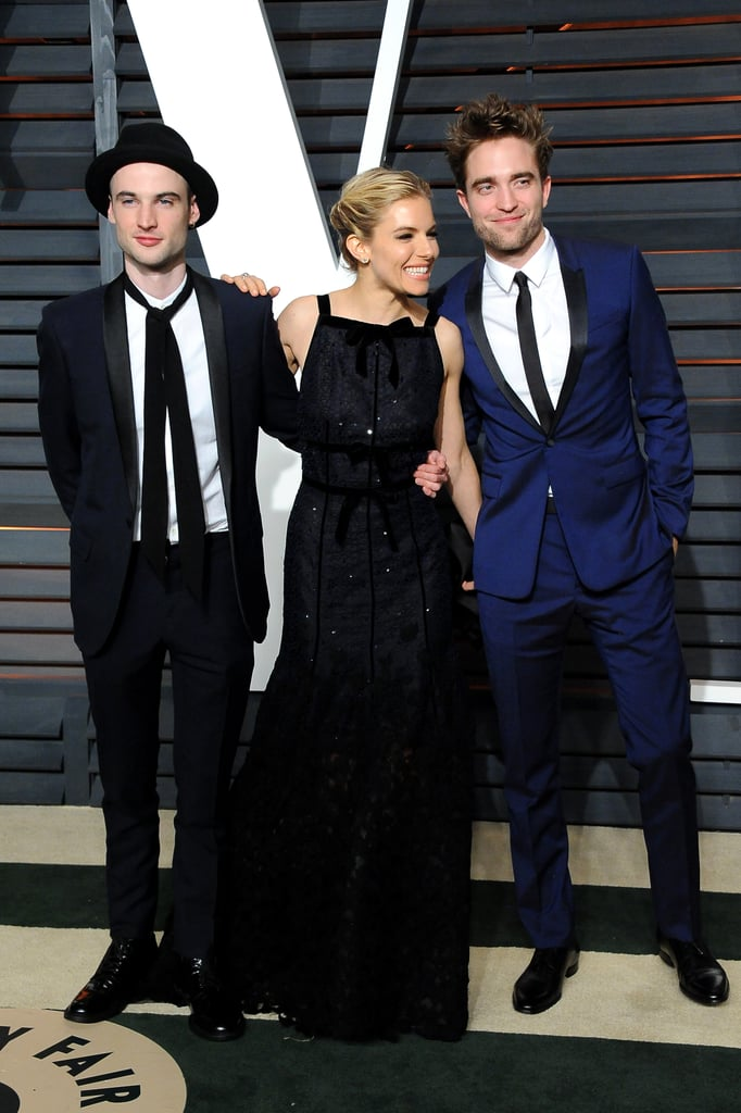 Plenty of A-listers from Beyoncé to Eddie Redmayne were hanging out at Vanity Fair's Oscars party, and among the crowd were a couple of good-looking Brits. Robert Pattinson arrived to the soiree with Sienna Miller and her husband, Tom Sturridge, who is one of Rob's best friends. The trio smiled for photos at the celebration, which was held in the Wallis Annenberg Center for the Performing Arts. Rob, who skipped the actual Academy Awards, wore a dark-navy suit with black lapels, while Sienna and Tom dressed in matching black. Keep reading to see more photos of Rob, and check out who else was at Vanity Fair's afterparty.