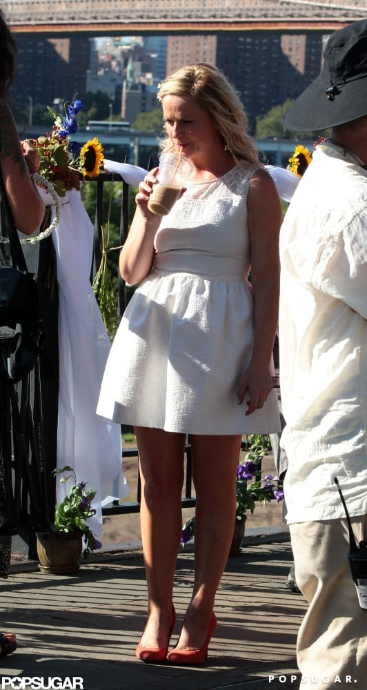 Amy Poehler sipped on a drink between takes.