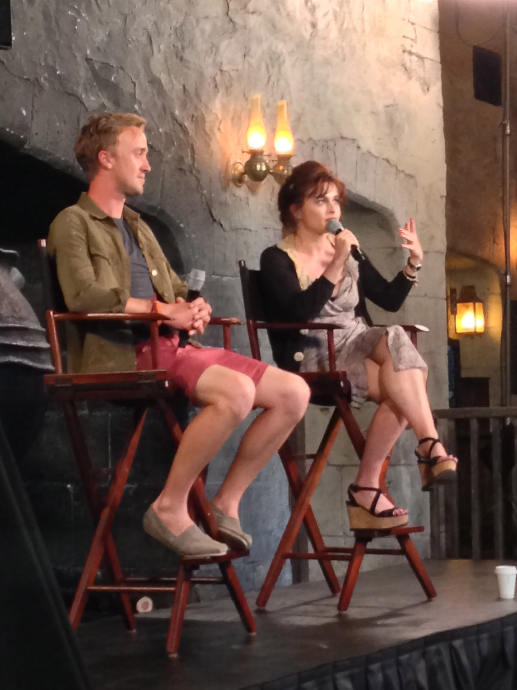 """Tom Felton and Helena Bonham Carter, who play villains Draco Malfoy and Bellatrix Lestrange, answered questions during a panel. The two are far from villainous in their real lives. In fact, Helena shared that her two children (with partner Tim Burton), Billy and Nell, were """"enchanted"""" with Diagon Alley. She added that Nell, who's 6, just started reading the first book."""