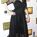 Christina Hendricks showed off her shape in a sheer black dress, nipped in to accentuate her waist, and finished with sheer sleeves and a see-through overlay.