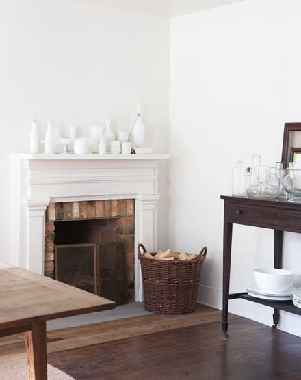 Lighten things up with white vases and sculptural objects on the mantel. By using a wicker basket for firewood, the feel of the space skews toward Summer rather than Winter.  Source