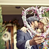 Kiss in Front of a Heart Made of Christmas Lights