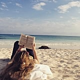 Suki Waterhouse cracked open a book on the beach.
