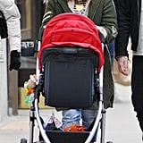 Drew Barrymore pushed baby Olive's stroller through NYC looking entirely cozy in a layered look, which included an olive-green fur-trim coat and a black-and-white beanie.
