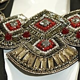 Embellished in sequins, beads, and a burst of poppy red, this is what statement jewelry is all about.