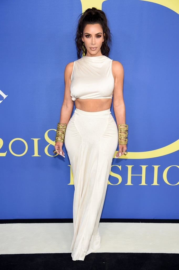 Kim Kardashian always knows how to make an entrance. The 37-year-old mogul walked the 2018 CFDA Awards carpet on June 4 to accept the council's first-ever influencer award, and of course she did it in style. Her two-piece top and skirt feature a high-cut neck and bare her toned abs. She paired the ensemble with gold statement cuffs for an overall goddess effect.  Kim jetted off to New York the night before with sisters Kourtney Kardashian and Kendall Jenner, ex-assistant Stephanie Shepherd, and fashion designer Virgil Abloh. She later walked the carpet with Kourtney while Kendall made her own appearance in a fuzzy lavender dress that we're still thinking about.      Related:                                                                                                           OMG — Kendall Jenner's Fuzzy Dress Has a Slit That Goes WAYYY Up