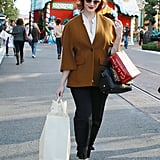 Mad Men's Christina Hendricks may not have stepped foot inside the holiday house behind her, but shopping at The Grove in LA during December is automatically festive.