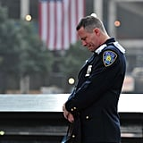 A police officer bowed his head during the 9/11 commemoration ceremonies in NYC.