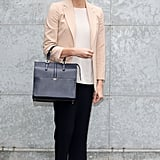 In February 2013, Princess Charlene wore black trousers with a white tee, blush blazer, and flats to the Giorgio Armani show.