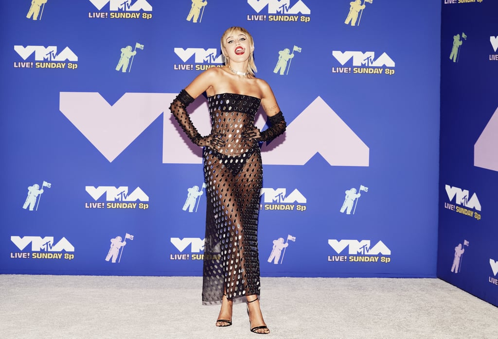 """Let's give Miley Cyrus a round of applause because she definitely *brought it* at the 2020 MTV VMAs. The singer, who is performing """"Midnight Sky,"""" stunned in a sparkly black Mugler dress that was completely sheer. (No shocker there since she's the queen of daring MTV VMAs red carpet looks.) She paired the see-through dress with matching black underwear, and the strapless number was covered with tiny silver mirrored embellishments that reflected with the camera flashes.  Miley's dress came with a pair of matching sheer gloves that featured black studs in place of the silver embellishments. As for her accessories, she styled the see-through dress with big gold hoops and a chain choker necklace. She slipped into a pair of black strappy heels to finish off her look. Keep reading to see her outfit ahead.      Related:                                                                                                           Joey King's MTV VMAs Outfit Has Us Singing """"Versace, Versace, Versace"""""""