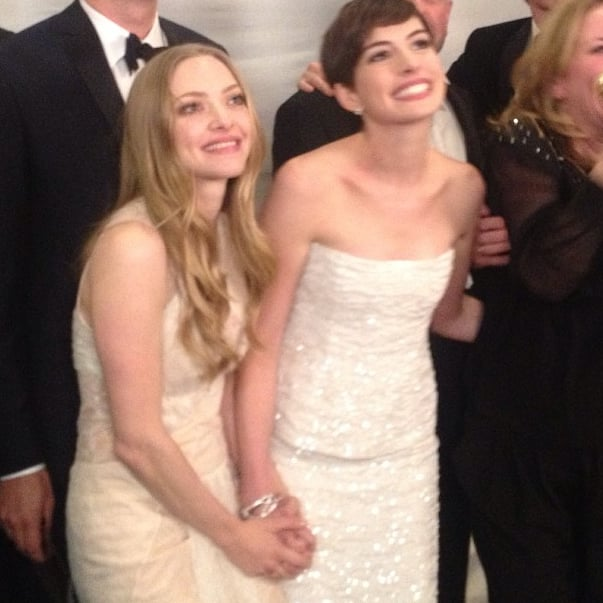 Amanda Seyfriend and Anne Hathaway held hands while celebrating Les Miserables's Golden Globes win. Source: Instagram user goldenglobes