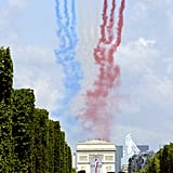 "The ""Patrouille de France"" alphajets color the sky with the French flag's blue, white, and red over the Champs-Elysees."