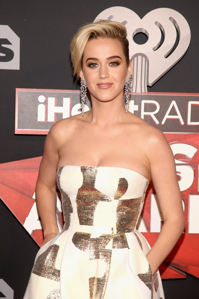 """Katy Perry shone bright at the iHeartRadio Music Awards in LA on Monday. The """"Chained to the Rhythm"""" singer stunned in a white and golden strapless gown, which paired perfectly with her new blonde pixie cut. Katy's fun outing marks her first appearance since her split from Orlando Bloom. After a little over a year of dating, the two called it quits in late February, and the duo's reps released a joint statement that said they would be """"taking respectful, loving space at this time."""" A couple days later, Katy addressed the split via Twitter, urging """"a new way of thinking"""" and insisting that """"no one's a victim or a villain."""" Orlando has yet to comment on the matter, but he was spotted chatting up women on the beach over the weekend."""