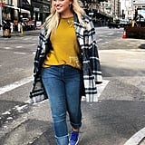 An Olive Green Sweater Under a Plaid Coat With Jeans and Sneakers