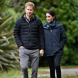 While in New Zealand, the Duchess of Sussex wrapped up in a raincoat, which she paired with black jeans, a scarf, and comfortable white trainers by Stella McCartney for Adidas.