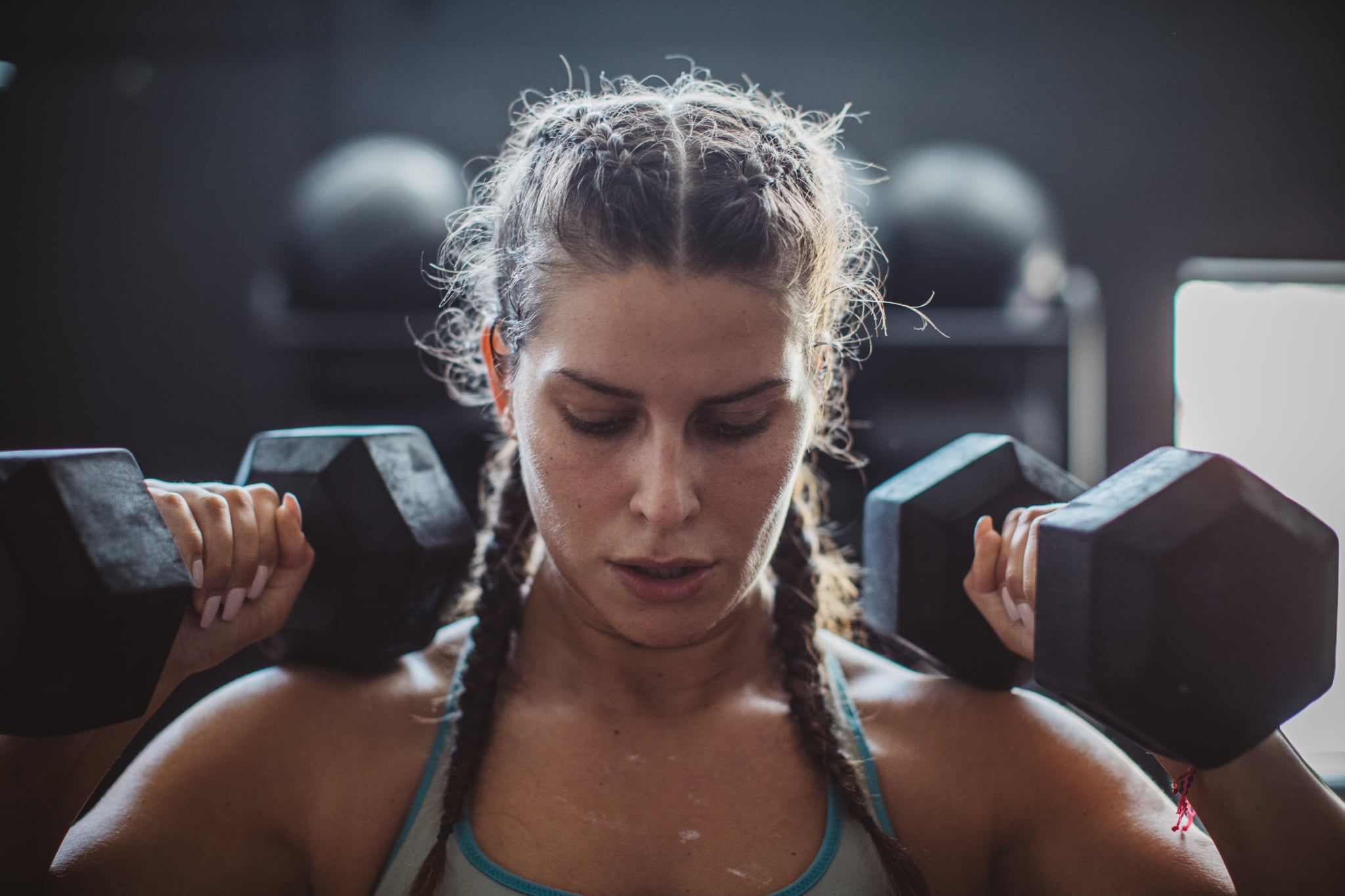 Woman weightlifting with dumbbells in gym