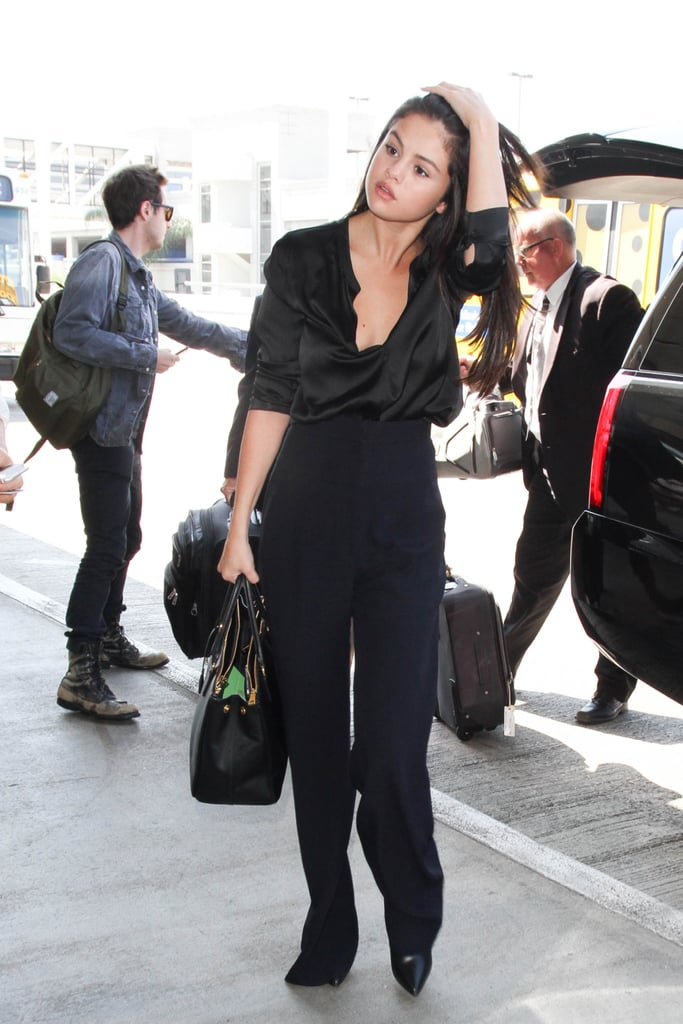 Selena styled her silk, open-front blouse with a pair of wide-leg high-waisted trousers. Her leather pointed-toe booties peeked out from beneath her pants as she walked confidently into LAX. Selena added a structured Prada Saffiano tote bag, a trusty, sophisticated staple for any trip.