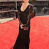 Miley Cyrus looked edgy but gorgeous in her Emilio Pucci dress, accessorized with an Edie Parker bag.