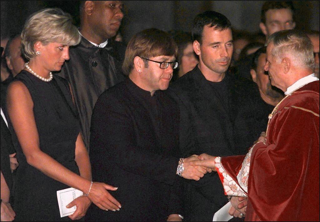 Archpriest Magio (R) shakes hands with British rock star Elton John standing next to Princess Diana (L) during the requiem mass for Italian fashion designer Gianni Versace at the Duomoin Milan 22 July 1997. Versace was gunned down in Miami Beach 15 July. EDS NOTE: Best quality available. (ELECTRONIC IMAGE) (Photo credit should read GERARD JULIEN/AFP/Getty Images)