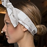 While the croissant bun spotted backstage at the Lela Rose runway show is one of our favorite options for styling second-day hair, it's also the perfect look to try if you're missing a hair tie as well (talk about a win-win). Even though this look originally featured a small hair elastic to bring the hair into a low ponytail before rolling it into a bun, you can skip that step entirely and choose a bandana to hold the hair in place and achieve the same effect.
