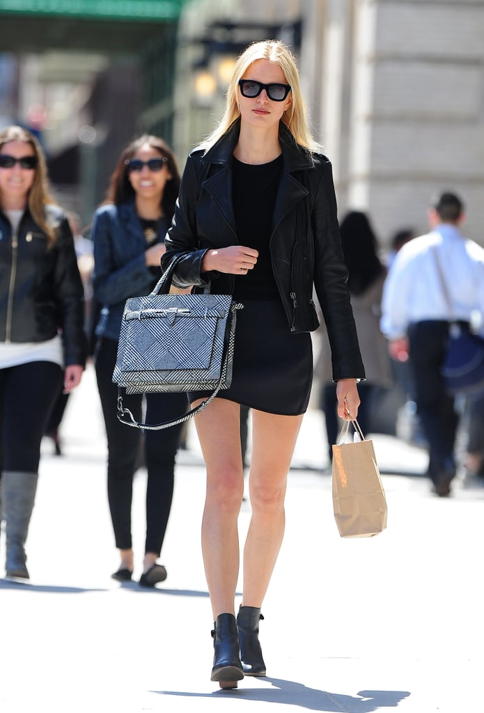 Karolina Kurkova made her presence known on the streets of NYC by sporting a black mini-dress with a black leather biker jacket, ankle boots, black sunglasses, and a black-and-white checkered bag.