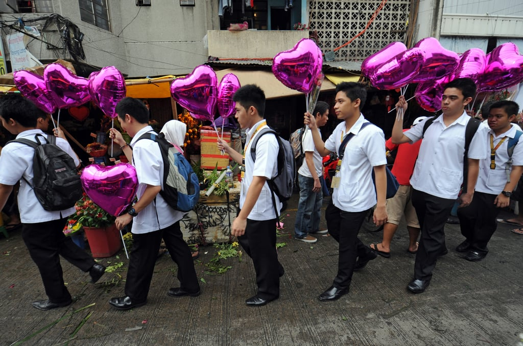 Students holding heart-shaped balloons walk past flower