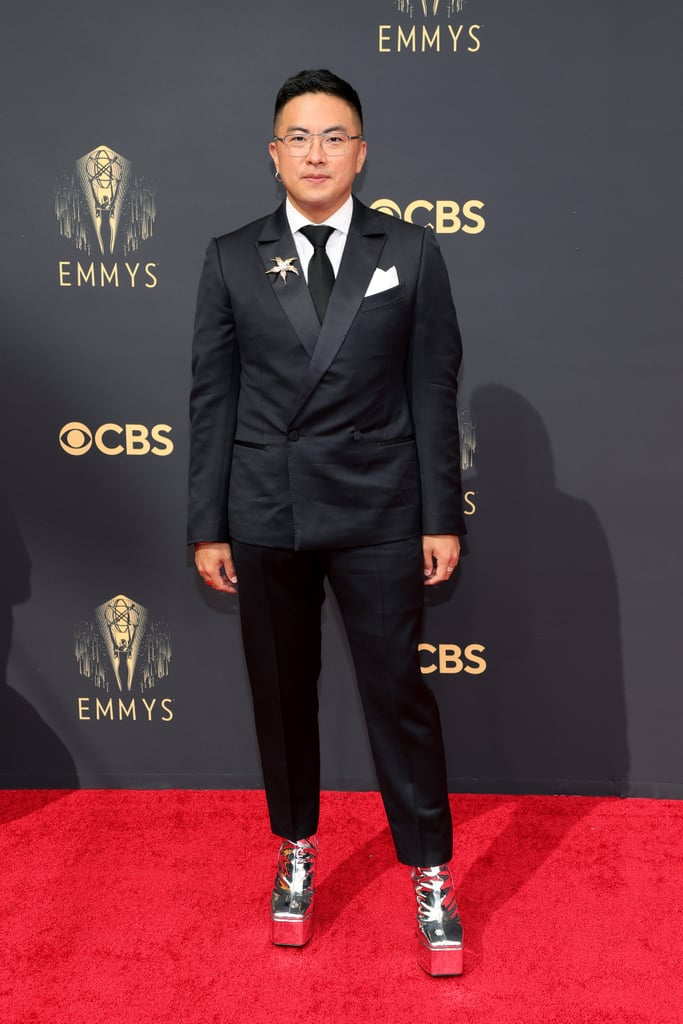 Bowen Yang made all other shoes irrelevant with his first-ever appearance at the Emmy Awards. The actor and Saturday Night Live cast member attended the award show on Sept. 19 wearing quite the intergalactic footwear: a pair of metallic silver platform heels by Brooklyn-based brand Syro.  A classic Ermenegildo Zegna suit served as the foundation of Bowen's outfit, which he also paired with a floral Tiffany & Co. brooch. Though he was certainly victorious on the red carpet, Bowen is also nominated for outstanding supporting actor in a comedy series, making him the first featured player to do so in the show's 46 seasons. Enjoy photos of his look ahead.