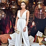 Olivia Culpo wearing a white jumpsuit with a matching clutch.
