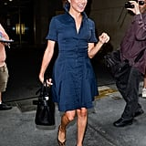 Meghan flawlessly pulled off a navy and black outfit by styling this formfitting shirt dress with a structured tote. She coordinated her pieces with leopard pumps in July 2016.