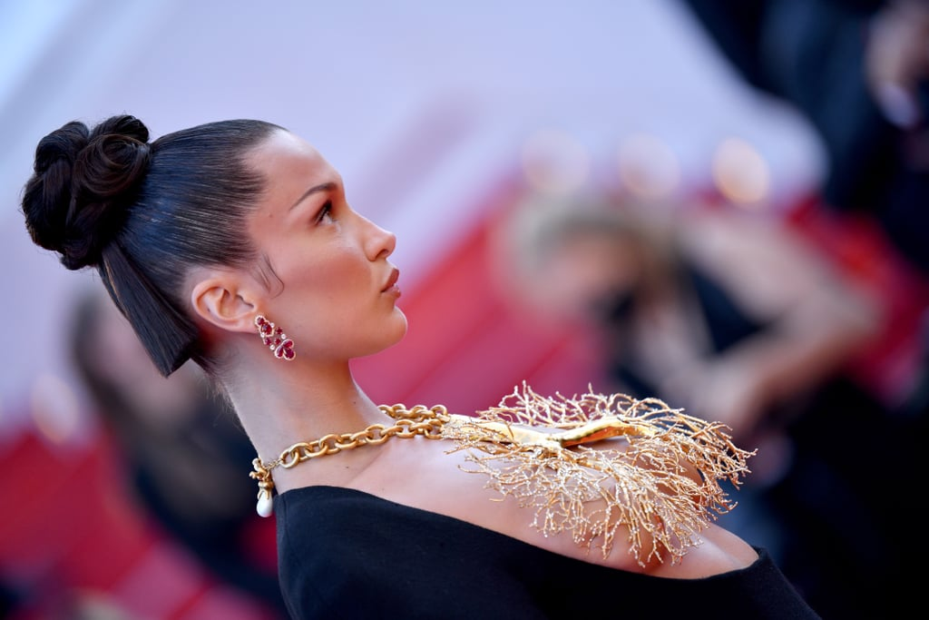 """Welcome to day two of me trying to wrap my head around Bella Hadid's bun. The model has inadvertently become the face of this year's Cannes Film Festival — turning heads in vintage Jean Paul Gaultier and giving her mystery boyfriend his grid debut — and her latest appearance was no less headline making. At the Tre Piani screening on July 11, Hadid wore a couture Schiaparelli gown with an open neckline and a gold, branched, lung-shaped statement necklace. Her hair was just as transfixing.  Styled by Peter Lux, the updo consisted of various small sections intertwined, almost like a braid. Two sections, however, were straightened and left to stick out and hang below the bun, like the Cynthia doll from Rugrats, except very chic. (No disrespect to Cynthia.) The updo also bore the same ethos behind the mullet: business in the front, party in the back. See the hairstyle from all angles ahead, and be sure to check back in on day three of me trying to wrap my head around it.       Related:                                                                                                           Andie MacDowell's """"Badass"""" Natural Gray Hair Makes Red Carpet Debut at Cannes Film Festival"""