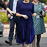 Meghan in a Navy Sweater and Pleated Skirt