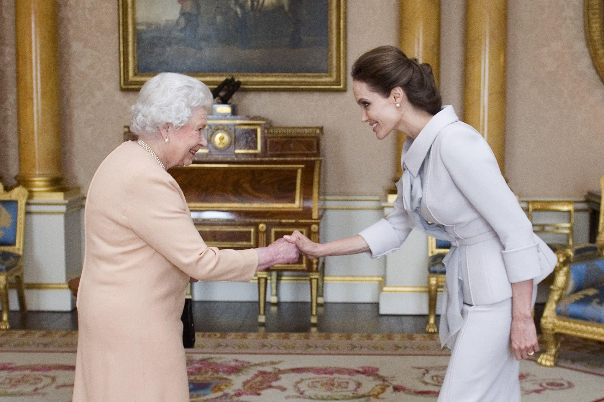 US actress Angelina Jolie (R) is presented with the Insignia of an Honorary Dame Grand Cross of the Most Distinguished Order of St Michael and St George by Britain's Queen Elizabeth II in the 1844 Room at Buckingham Palace in central London, on October 10, 2014. Angelina Jolie was awarded an honorary damehood (DCMG) for services to UK foreign policy and the campaign to end war zone sexual violence. AFP PHOTO/Anthony Devlin/POOL        (Photo credit should read Anthony Devlin/AFP/Getty Images)