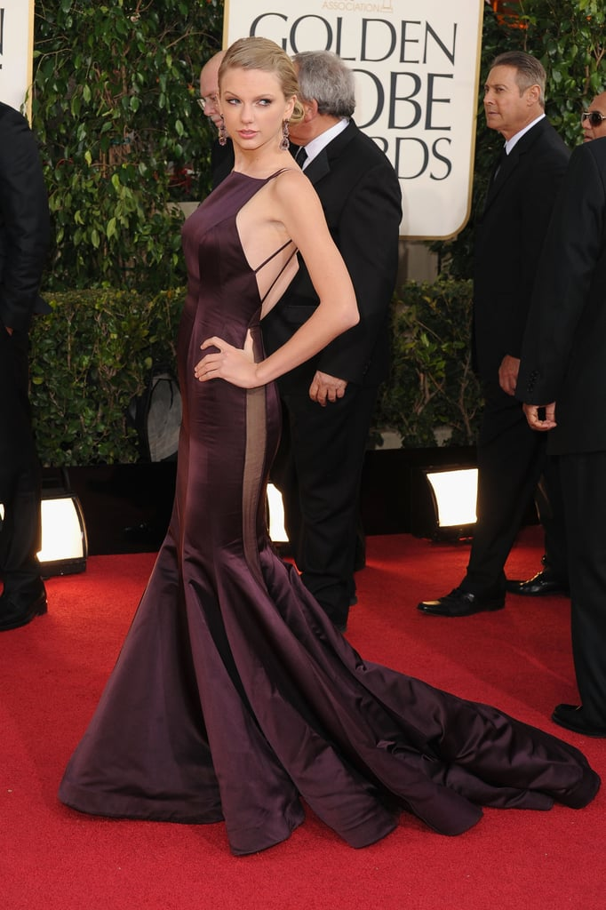 "Taylor Swift walked the red carpet at the 2013 Golden Globes in LA today. She wore a backless Donna Karan Atelier gown and had her hair pulled back. Taylor is nominated for best original song in a motion picture for ""Safe and Sound"" from the Hunger Games soundtrack. Taylor is up against Adele, Jon Bon Jovi and the Les Misérables cast for the award. Be sure to check out our red carpet fashion and beauty polls to weigh in on Taylor's look and much more Golden Globes fashion."
