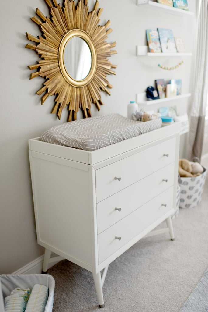 """""""The wallpaper I created for Samuel is my favorite part of the nursery. Before he was born, I pictured him in his room and knowing I made something special for him put a smile on my face,"""" Catherine said. Mid-Century 3 Drawer French White Dresser ($729, originally $949) Sunburst Round Mirror ($346) Picture Ledge Floating Wall Shelf ($21, originally $45)"""