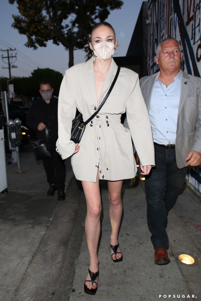 Sophie Turner's style means business. On May 7, the Game of Thrones actress visited Craig's in Hollywood with her husband Joe Jonas and his brothers, Nick and Kevin, for dinner. Of course, her outfit went above and beyond your typical night-out ensemble.  Sophie opted for a chic broad-shoulder blazer dress with a drawstring waist, and matched the look with a neutral face mask. She tied the ensemble together with Wandler statement sandals and a black cross-body bag. Dare I take notes for my next outing with the in-laws? My fashion game could surely use a few tips from Sophie's style choices, that's for sure. Get a closer look at her entire look, plus Joe's accompanying outfit, in the photos ahead.       Related:                                                                                                           Sophie Turner's 14 Best Moments in Louis Vuitton, According to the Brand